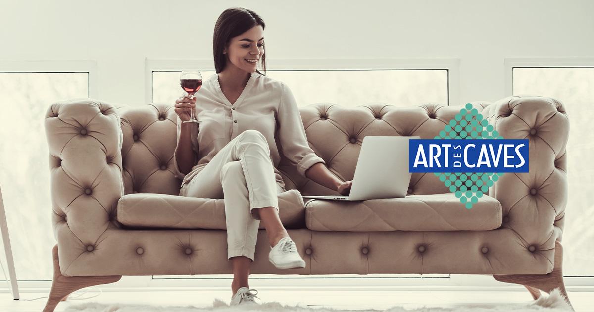 Uma mulher sentada no sofá com uma taça de vinho na mão, enquanto pesquisa no computador pela melhor adega climatizada.